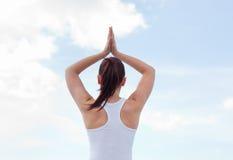 Opinión trasera una mujer joven que hace yoga Imagen de archivo