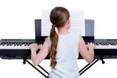 Opinión trasera una niña que juega el piano eléctrico. Imagenes de archivo