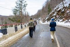 Opinión trasera viajeros en el camino de la montaña en invierno Fotos de archivo libres de regalías
