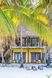 Opinión tropical del chalet a través de las palmeras en la playa arenosa exótica Fotografía de archivo