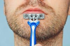 Opinión un hombre barbudo joven con una maquinilla de afeitar brutal cara en el fondo azul cerdas melenudas ásperas grandes en la Imágenes de archivo libres de regalías