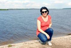 Opinión una mujer feliz que se sienta en la orilla del río fotografía de archivo