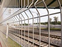 Opinión Unfocused del ferrocarril a través de la cerca del metal Imagen de archivo libre de regalías