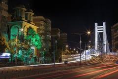 Opinión urbana de la noche con el tranvía y el puente de Basarab Foto de archivo