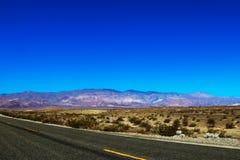 Opinión vertical clásica del panorama de un camino recto sin fin que corre con el paisaje estéril del sudoeste americano con foto de archivo