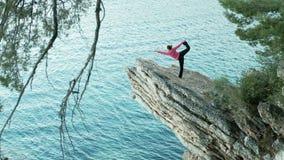 Opiniões de Stunning do treinador da ioga o penhasco e uma mulher que esteja fazendo exercícios no mar Em uma pedra alta da borda video estoque
