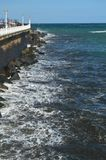 Opiniões maravilhosas o San Sebastian Bay de seus passeio e ondas fortes que carregam contra seu quebra-mar em San Sebastian LAN imagem de stock