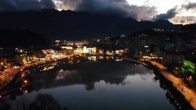 Opini?n del paisaje de la ciudad de la noche con el fondo de la monta?a y reflexi?n del cielo nublado en el agua situada en SAPA, metrajes