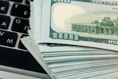 Opini?n del primer de cientos billetes de banco del d?lar que mienten en el teclado del ordenador port?til imagenes de archivo