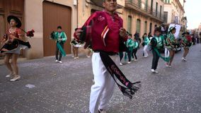 Opini?n del primer gente en los trajes verdes y negros del carnaval que bailan en la calle Arte Bandas de la calle del carnaval almacen de video