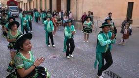 Opini?n del primer gente en los trajes verdes y negros del carnaval que bailan en la calle Arte Bandas de la calle del carnaval metrajes