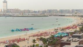 Opini?n a?rea la playa y los turistas que caminan y que toman el sol el d?a de fiesta en timelapse de JBR en Dubai, UAE almacen de video