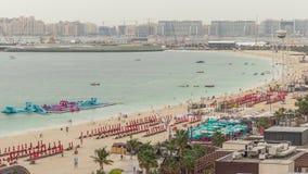 Opini?n a?rea la playa y los turistas que caminan y que toman el sol el d?a de fiesta en timelapse de JBR en Dubai, UAE metrajes
