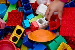 Opini?n superior sobre ladrillos multicolores del juguete y otros juguetes con children' manos de s que juegan con ellos Per imágenes de archivo libres de regalías