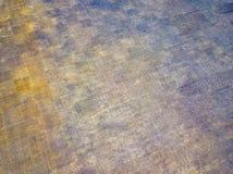Opini?n superior sobre un fondo modelado ?spero de una textura del amarillo, gris y beige con los remiendos y las rayas en el cam imágenes de archivo libres de regalías