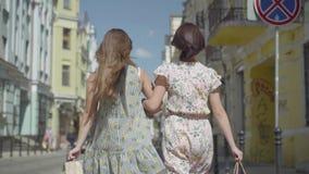 Opini?n trasera dos mujeres que caminan con los panieres Chicas jóvenes que llevan los vestidos elegantes del verano que gozan co metrajes