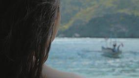 Opini?n trasera la chica joven que se relaja en una playa tropical en d?a soleado r almacen de metraje de vídeo