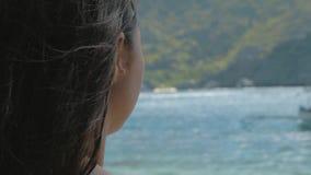 Opini?n trasera la chica joven que se relaja en una playa tropical en d?a soleado r metrajes
