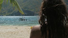 Opini?n trasera la chica joven que se relaja en una playa tropical en d?a soleado r almacen de video