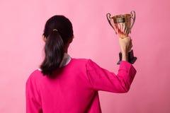 Opini?n trasera la mujer asi?tica joven acertada que sostiene un trofeo imagen de archivo libre de regalías