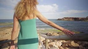 Opini?n trasera una mujer que camina hacia el mar en las escaleras hermosas almacen de metraje de vídeo