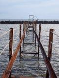 Opini?o de perspectiva de um molhe oxidado quebrado abandonado do ferro que corre ao mar imagens de stock royalty free