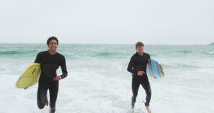 Opini?o dianteira dois surfistas masculinos que correm junto com a prancha na praia 4k video estoque