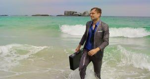 Opini?o dianteira o homem de neg?cios caucasiano que anda com a pasta no mar na praia 4k vídeos de arquivo