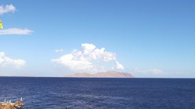 Opini?o do mar no dia de ver?o agrad?vel: c?u azul com nuvens pequenas, ?gua do mar azul limpa e as ondas lisas, linha clara do h filme