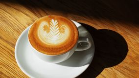 Opini?o superior de copo de caf? da arte do Latte ou do cappuccino na tabela de madeira com luz solar no caf? fotos de stock