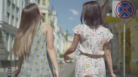 Opini?o traseira duas mulheres de passeio com sacos de compras Moças que vestem os vestidos à moda do verão que apreciam com desp video estoque