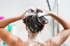 Opini?o traseira a mulher nova que lava seu cabelo imagens de stock