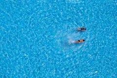 Opinión aérea dos muchachas que nadan en la piscina Imagen de archivo
