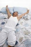 Opinión de alto ángulo el hombre de reclinación que estira sus brazos Fotos de archivo