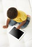 Opinión de arriba el muchacho en Sofa Playing With Digital Tablet Fotografía de archivo