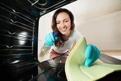 Opinión de la limpieza de la mujer por dentro del horno Fotos de archivo libres de regalías