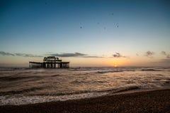 Opinión de la puesta del sol sobre el embarcadero y la playa viejos de Brighton Foto de archivo