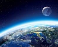 Opinión de la tierra y de la luna del espacio en la noche Foto de archivo libre de regalías