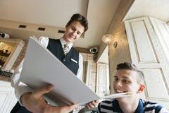Opinión de ángulo bajo el camarero que muestra el menú al cliente masculino en restaurante Imágenes de archivo libres de regalías