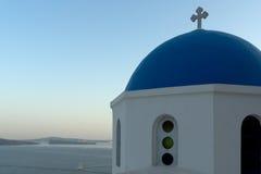 Opinión de Twinlight de la iglesia con el tejado azul en la ciudad de Oia y del panorama a la isla de Santorini, Thira, Grecia Fotos de archivo
