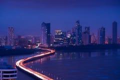 Opinión del horizonte de la noche de ciudad de Panamá de los coches del tráfico en la carretera Imagen de archivo libre de regalías