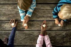 Opinión superior cuatro niños de razas mixtas cada tenencia un mármol h Imagen de archivo libre de regalías