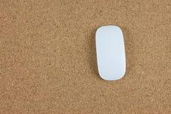 Opinión superior el ratón inalámbrico del ordenador en tablero marrón del corcho Imagen de archivo libre de regalías