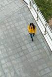 Opinión superior la mujer que camina en la calle y la charla al teléfono móvil Fotografía de archivo libre de regalías