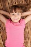 Opinión superior una niña sonriente que miente encendido detrás Imagenes de archivo