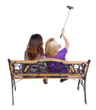 Opinión trasera dos mujeres para hacer un retrato del palillo del selfie que se sienta en el banco Fotografía de archivo libre de regalías