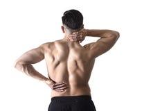 Opinión trasera el hombre joven con el cuerpo muscular que lleva a cabo su dolor espinal del cuello y del sufrimiento de espalda Foto de archivo libre de regalías