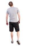 Opinión trasera el hombre que camina en pantalones cortos y zapatillas de deporte Imagen de archivo