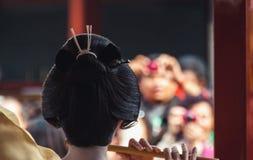 Opinión trasera una mujer vestida como geisha que juega música Imágenes de archivo libres de regalías