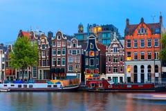 Opinião da cidade da noite do canal de Amsterdão com casas holandesas Fotos de Stock Royalty Free